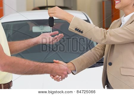 Businesswoman giving key while shaking a customer hand at new car showroom