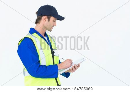 Handsome supervisor writing notes on clipboard over white background