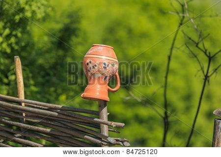 Traditional Ukrainian clay pot on rural fence an summer time