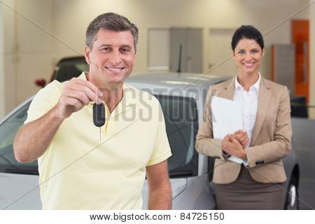 Smiling customer showing his new car key at new car showroom