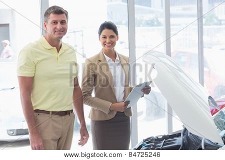 Businesswoman and customer looking at a car engine at new car showroom