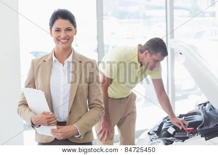 Smiling businesswoman holding a clipboard at new car showroom