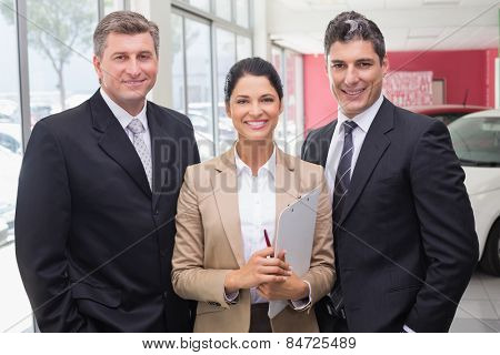 Smiling business team standing in a line at new car showroom