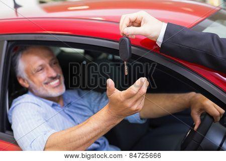 Smiling man driving a car while salesman his giving key at new car showroom