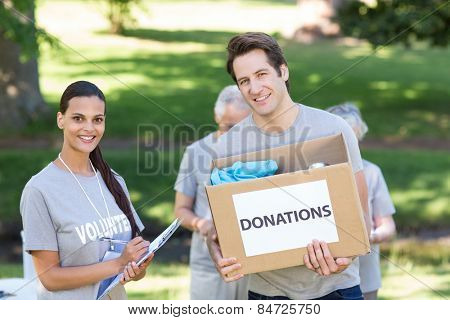 Happy volunteer man holding donation box on a sunny day