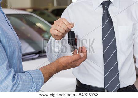 Businessman giving car key to customer at new car showroom