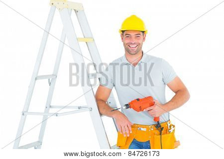 Portrait of happy handyman with power drill leaning on ladder over white background