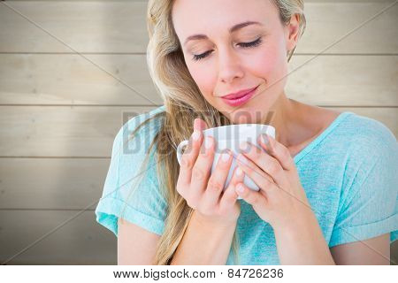 Smiling blonde with hot beverage relaxing against bleached wooden planks background