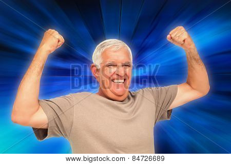 Portrait of a cheerful senior man with clenched fists against abstract background