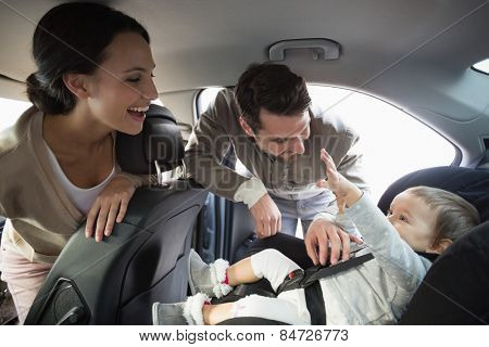 Parents securing baby in the car seat in their car