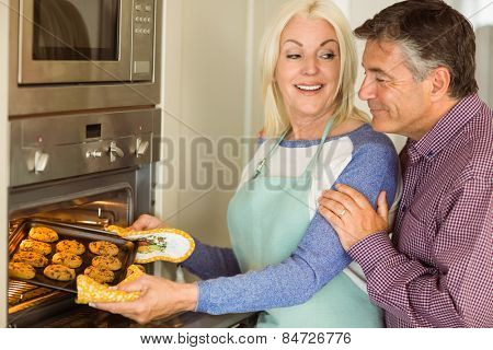 Woman taking tray of fresh cookies out of oven with husband at home in the kitchen