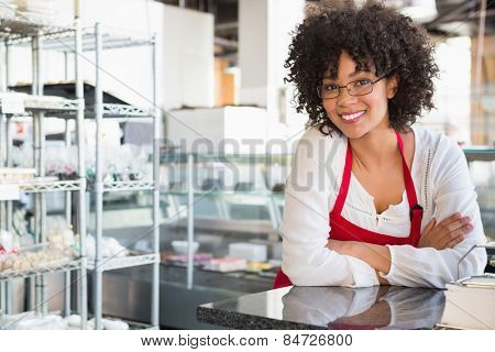 Smiling waitress with glasses leaning on counter at the bakery