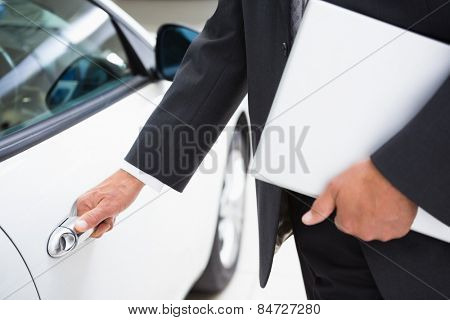 Man holding a car door handles while holding clipboard at new car showroom