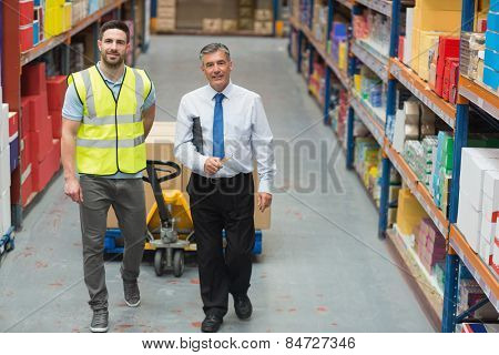 Warehouse worker talking with his manager in a large warehouse