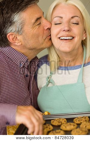 Mature blonde holding fresh cookies with husband kissing her at home in the kitchen