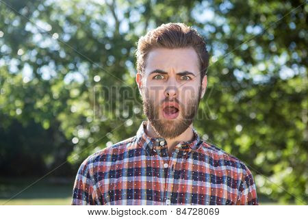Shocked hipster looking at camera on a summers day