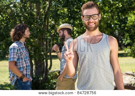 Hipster smiling at camera in the park on a summers day