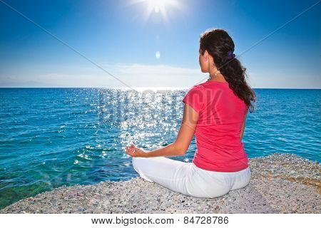 Relaxed young brunette woman sitting on a deserted tropical beach at sunrise. Greece.