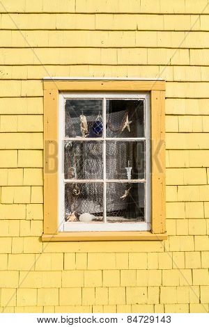 Quaint old window decorated in a nautical theme with fish net, shells, star fish and other things from the sea.
