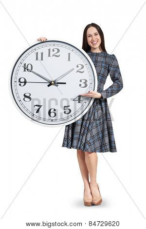 smiley beautiful woman holding big white clock and pointing at the time. isolated on white background
