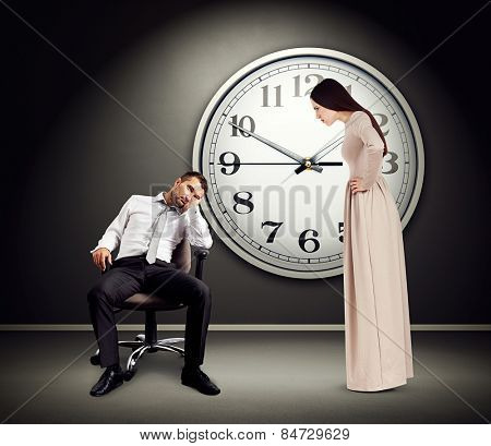 angry woman staring at lazy man on chair. photo in empty dark room with big white clock on the wall