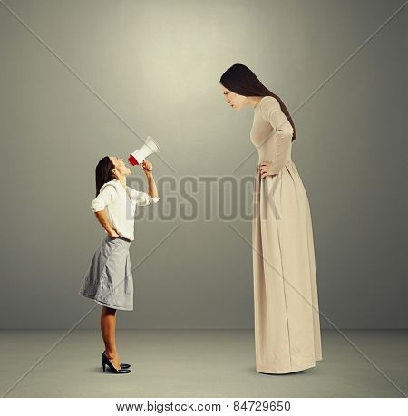 angry woman in long dress staring at small screaming woman with megaphone. photo over dark background