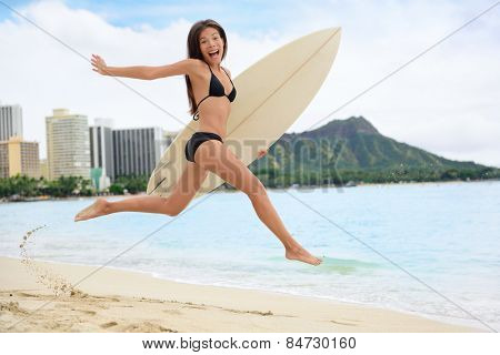 Surfing surfer happy having fun with surfboard jumping funny making excited face expression. Female bikini woman healthy active water sport lifestyle. Asian Caucasian model on Waikiki, Oahu, Hawaii.