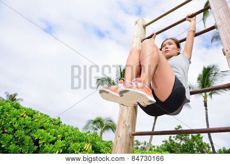 Core cross training fit woman doing abs exercises on beach on fitness vertical ladder rack. Young active athlete working out abs muscles outside.