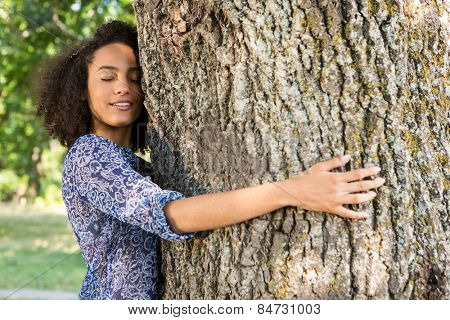 Pretty young woman hugging a tree on a summers day