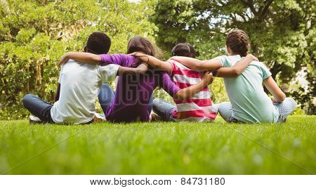 Rear view of children sitting with arms around at the park