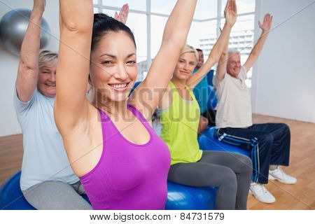 Portrait of happy people sitting on exercise balls with hands raised in fitness class