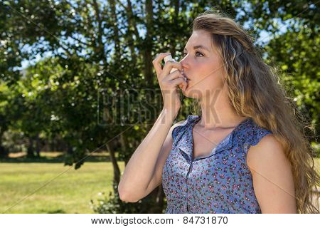 Pretty blonde using her inhaler on a summers day