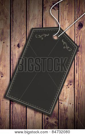 Elegant dark grey tag against wooden planks background