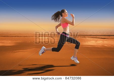 Full length of healthy woman jogging against hazy blue sky