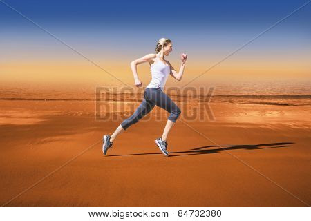 Pretty fit blonde jogging against hazy blue sky
