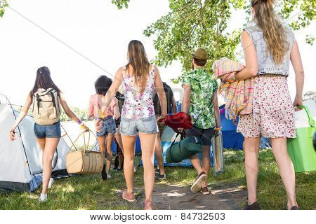 Excited friends arriving at music festival on a summers day