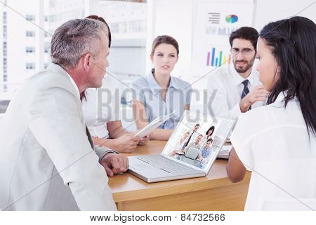 Happy business people gathered around laptop looking at camera against business team discussing work details