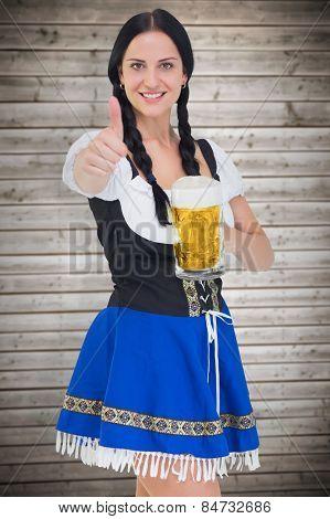 Pretty oktoberfest girl holding beer tankard against wooden planks background