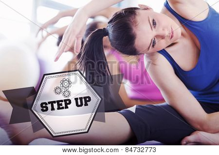 The word step up and class and instructor doing stretching pilate exercises against hexagon