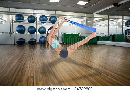 Fit young woman exercising with a blue yoga belt against large empty fitness studio with shelf of exercise balls