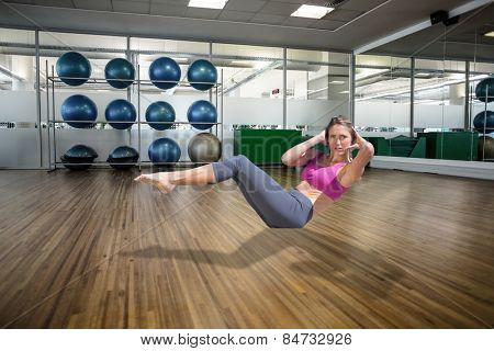 Focused fit blonde doing yoga on the beach against large empty fitness studio with shelf of exercise balls