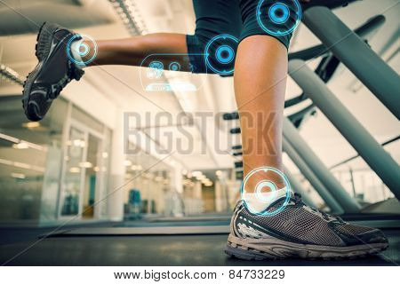 Fit woman running on the treadmill against fitness interface