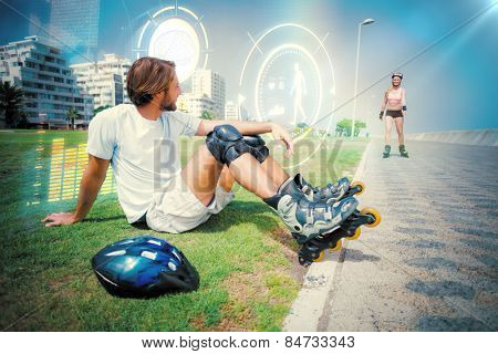 Fit man getting ready to roller blade against fitness interface
