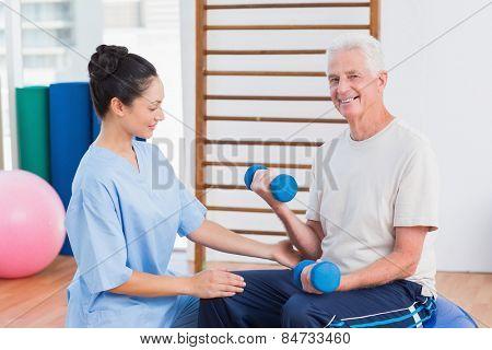 Female instructor assisting senior man in lifting dumbbells at gym