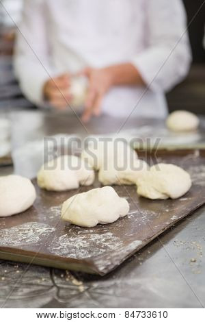Baker kneading uncooked dough on worktop in the kitchen of the bakery