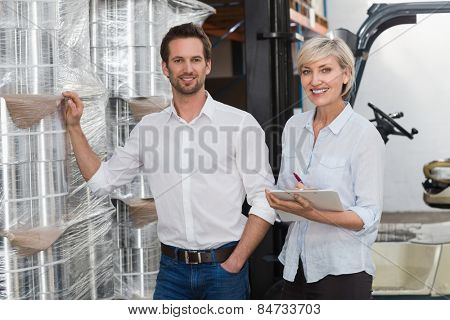 Smiling warehouse managers checking inventory in a large warehouse