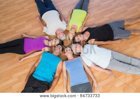 High angle view of fit people lying in circle on hardwood floor at gym