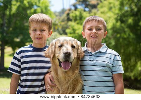 Little boys with their dog in the park on a sunny day