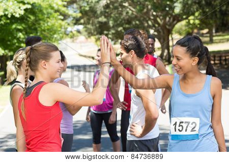 Fit women high fiving before race on a sunny day