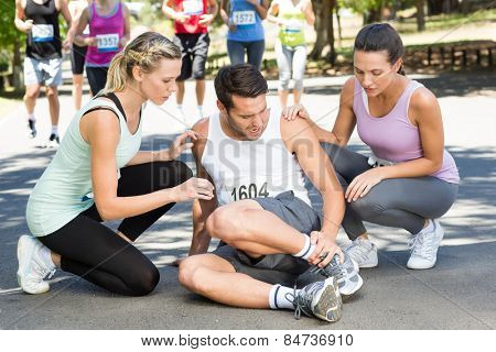 Man with injured ankle during race in park on a sunny day